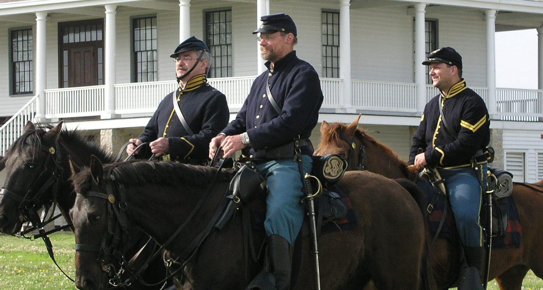 Three men on horseback dressed as Calvary solders next to the white Post hospital.